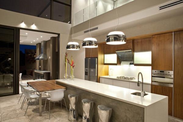 Khu vực bếp nấu cần nhiều ánh sáng, ngược lại, khu vực bàn ăn thoáng rộng nên sử dụng đèn chùm để tạo sự ấm cúng, riêng tư.