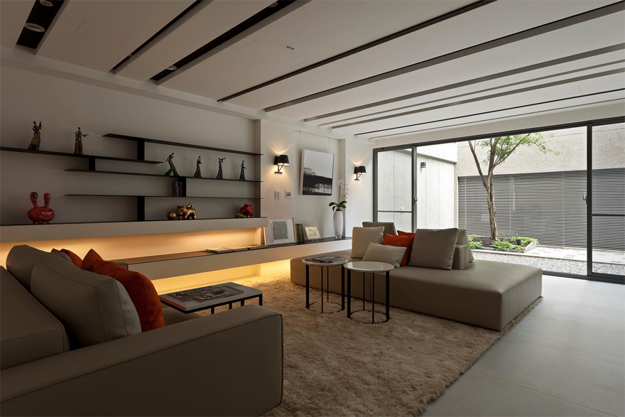 Phòng khách đơn giản với gam màu trắng - be và những đường song song trên trần, tường, sàn tạo cảm giác yên tĩnh kết hợp với cửa kính lớn, đem ánh sáng tư nhiên tràn ngập trong căn phòng